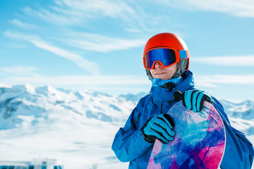 Photo of sportive man in helmet looking into camera with snowboard on background of snowy hill