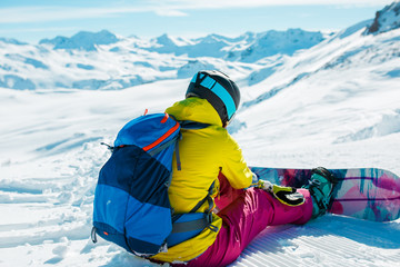 Image from back of woman in helmet with backpack on snow with snowboard