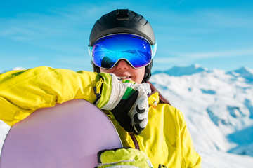 Portrait of smiling brunette in helmet and mask with snowboard on background of snowy hills