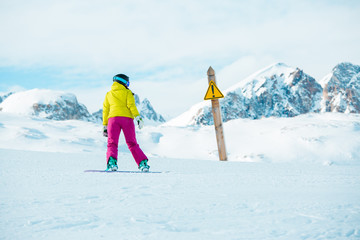 Picture of snowboarder woman wearing helmet at warning sign on mountain