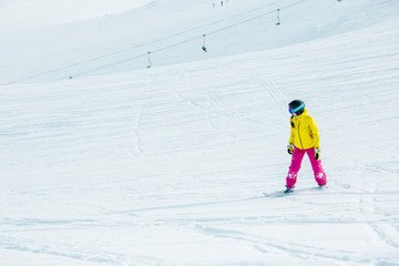 Image of young athletic girl wearing helmet in sports clothes snowboarding