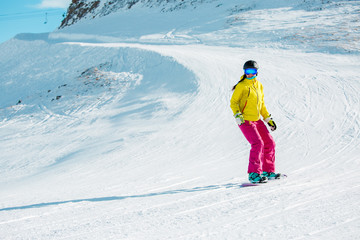 Picture of sports girl in helmet riding snowboard from mountain slope