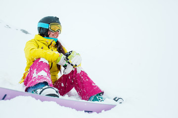 Photo of sporty smiling woman in helmet and mask with snowboard sitting on slope of snowy hill