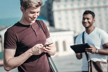 Internet addicted. Happy positive young man smiling and holding his smartphone while using social media