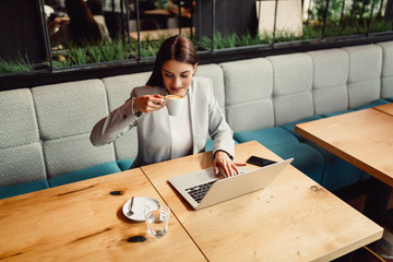 Beautiful businesswoman enjoying a coffee in front of her laptop computer