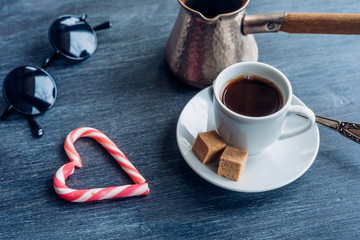 A cup of coffee on the table, turkish coffee pot, heart from Lolypop and cane sugar
