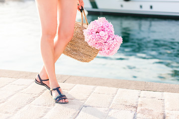 Girl with straw bag and pink flowers hydrangea. Traveler has vacation in sea resort near yacht port at sunset.