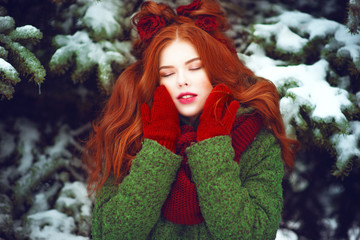 Close up portrait of beautiful red haired girl with creative hairstyle decorated with knitted flowers wearing red knitted mittens and scarf posing with closed eyes in front of snow covered firtrees