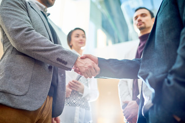 Mid-section of two successful business people shaking hands after beneficial deal, people in background