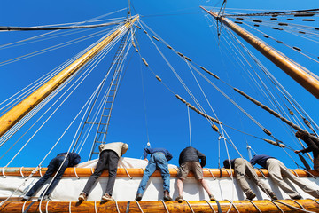 Crew leans over the side of a big sailboat to raise the heavy sail on a tall ship at sea. Takes six strong people to hoist the canvas sail. Theme for teamwork, cooperation