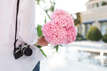 Man with pink flower hydrangea and film photo camera is waiting woman on romantic date in traveling at sunset in city park. Boy is wearing in casual white shirt outdoor.