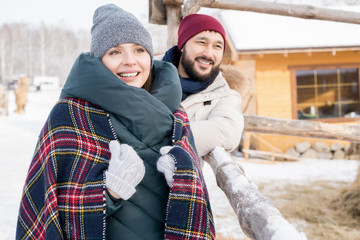 Portrait of modern young couple enjoying winter vacation together walking in nature at ski resort, copy space