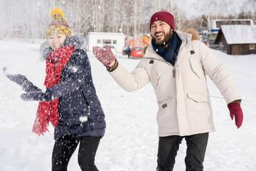 Portrait of young Asian couple having fun in snow enjoying nice winter days outdoors on ski resort