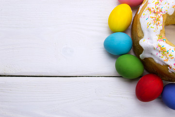 Easter eggs and easter cake on white wooden background