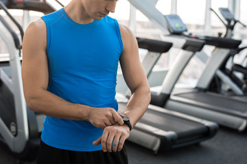 Mid section portrait of unrecognizable muscular man checking fitness tracker after working out in gym, copy space