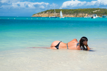 Woman with sexi ass lie in transparent sea in antigua