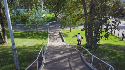Aggressive inline roller blader grind on rail in skatepark outside. Clip. Summer extreme sport exercising outdoor in skate park. Skater guy grinding on railing in park. Cool activity hobby for young