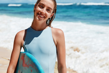 Satisfied happy female surfer being glad after going in for sport, stands wet against ocean view with surfing board, smiles happily at camera. Joyful sporty woman in bathing suit. Active rest concept