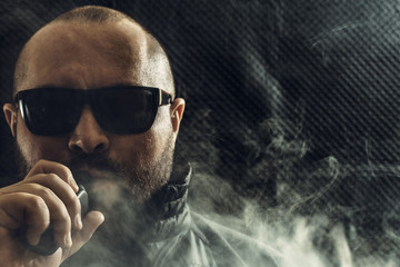 Portrait of smoker man in sun glasses vaping e-cigarette with e-liquid. Vape concept