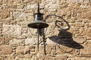 Fotomurales - Decorative black street lamp (lantern) and its shadow on historical stone wall in Cunda (Alibey) island.