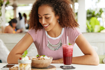 Happy African American female rests at coffee shop, looks at smart phone with anticipation, waits for boyfriend`s call, being in good mood. Dark skinned young woman has dinner in cozy restaurant