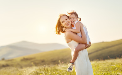 Happy family in summer outdoors.   mother  hug child daughter and laughing
