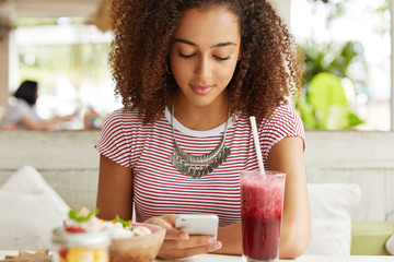 Attractive woman with curly hairstyle reads incoming notification from network on mobile phone, connected to wireless internet at cafeteria, drinks cold smoothie and eats dessert. Leisure concept