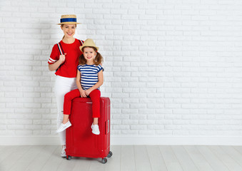 concept travel and tourism. mother and child daughter with suitcase near wall