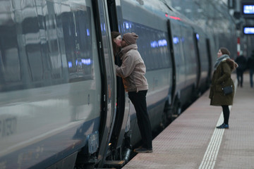 A couple kisses before a train leaves, at the Gdynia Glowna train station in Gdynia