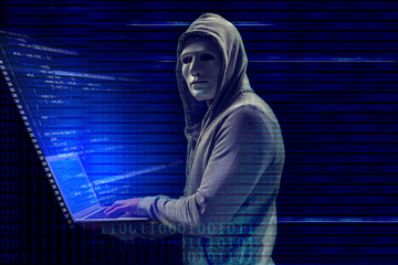 Hacker in mask with laptop on dark background