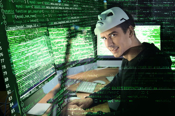 Hacker with mask using computer in darkness. Concept of cyber attack and security