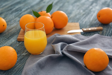 Glass with fresh orange juice and fruit on wooden table