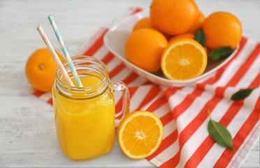 Mason jar with fresh orange juice and fruit on wooden table