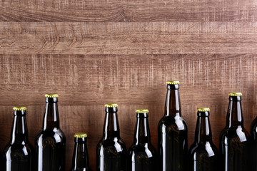 Fresh beer in glass bottles on wooden background