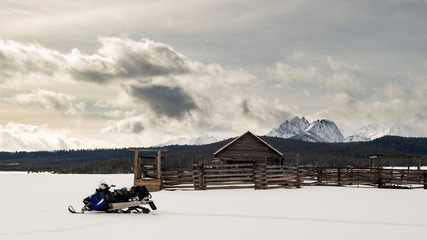 Snowmobile parked at an old Idaho corral in winter with sawtooth mountains