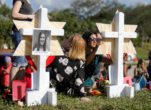A community member writes on a Star of David for one of the victims of the shooting at Marjory Stoneman Douglas High School at a memorial at the school in Parkland