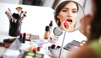 Young beautiful woman making make-up near mirror,sitting at the desk Wall mural