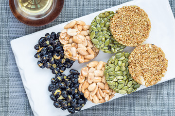 Korean traditional sweet snacks with peanuts, pumpkin seeds, black soybeans and chinese buckwheat. Top view, horizontal