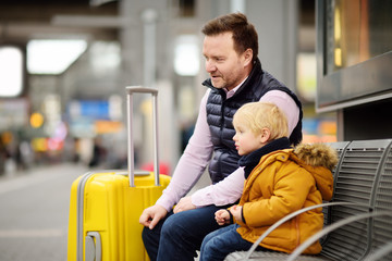 Little boy and his father waiting express train on railway station platform or waiting their flight at the airport