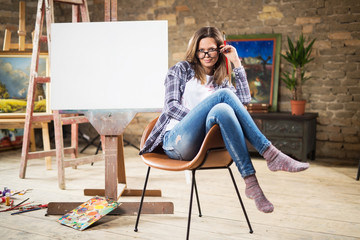 Beautiful young woman in painting studio