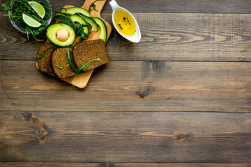 Breakfast for safety weight loss. Avocado toast with rye bread, lime, olive oil and greens on dark wooden background top view space for text