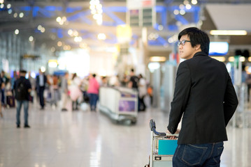 Young asian man with his luggage on airport trolley waiting for check in at airline counter in the international airport terminal, business travel concept