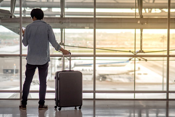 Young Asian man standing with suitcase luggage and holding smartphone in the international airport terminal, travel lifestyle concept