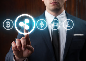 Businessman pressing ripple icon choosing from other cryptocurrency. Bitcoin, ripple, litecoin, dash, ethereum