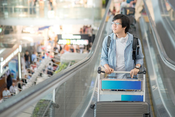 Young Asian man with airport trolley on escalator, walking to check-in counter in the international airport terminal. travel abroad on vacation