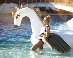 woman standing on sea shore beach near resort hotel with giant inflatable unicorn pegasus float mattress in white bikini