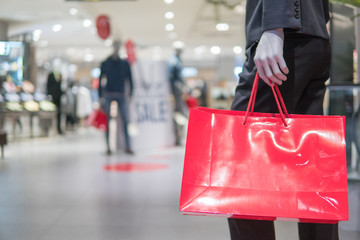 Close up clothing mannequin  holding red shopping bag at shopping mall,mock up and business shopping concept