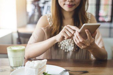 Young woman using smart phone and eating cake in cafe