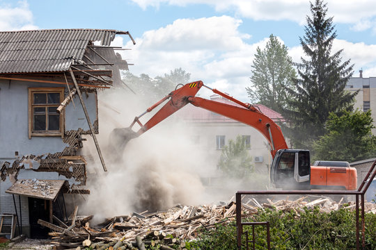 excavator working at the demolition of an old residential building