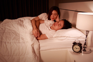 sleeping man lying on bed with woman concerned comforting him at night